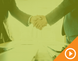 Two people in business suits shaking hands behind a green transparency with a white play button on top of an orange triangle in the bottom right corner