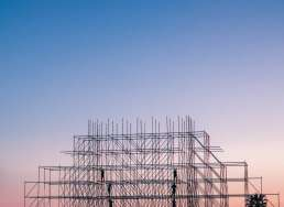 Framework for a building against a purple sunset