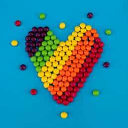 Rainbow heart made of candy on blue background