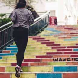Woman jogging up colorful steps