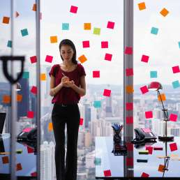 Secretary working in modern office in skyscraper, writing and sticking adhesive notes with tasks on window.
