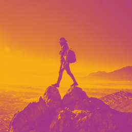 Orange and purple photo of man standing over gap in mountains