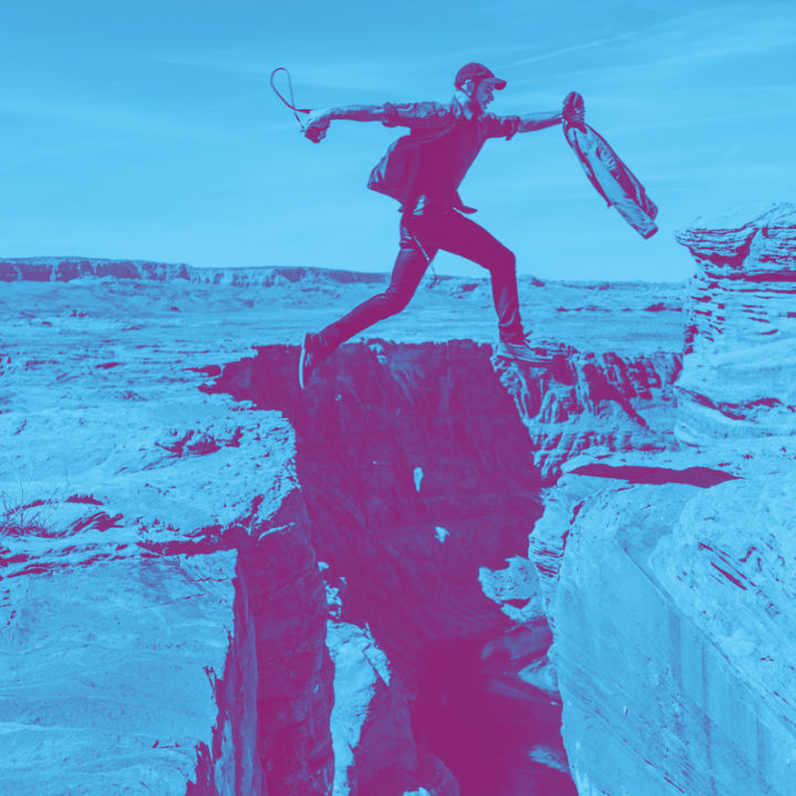 Blue and purple photo of man jumping over gap in mountain