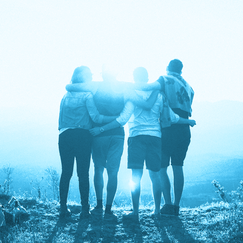 Blue and white photo of four people staring into the sunset